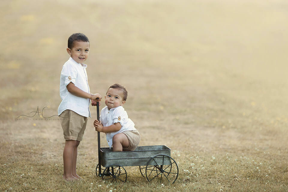 London Sibling Photos | portrait of 2 brothers playing outdoor with metal trolley