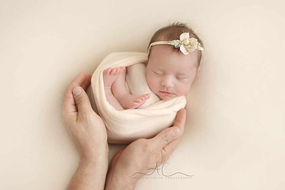 Professional Bromley Newborn Images | newborn baby girl sleeping in father's hands