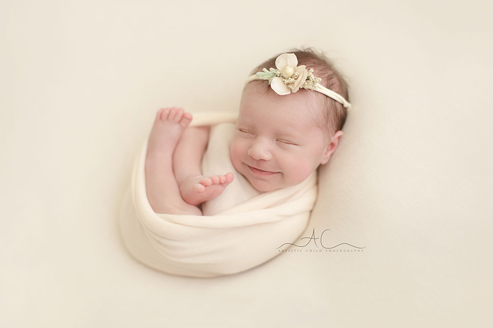 Professional Bromley Newborn Images | newborn baby girl smiling during a professional photo session