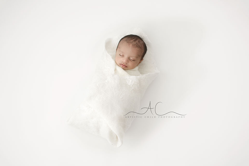 Professional London Newborn Photography Offer | a simple portait of a newborn baby boy swadlled