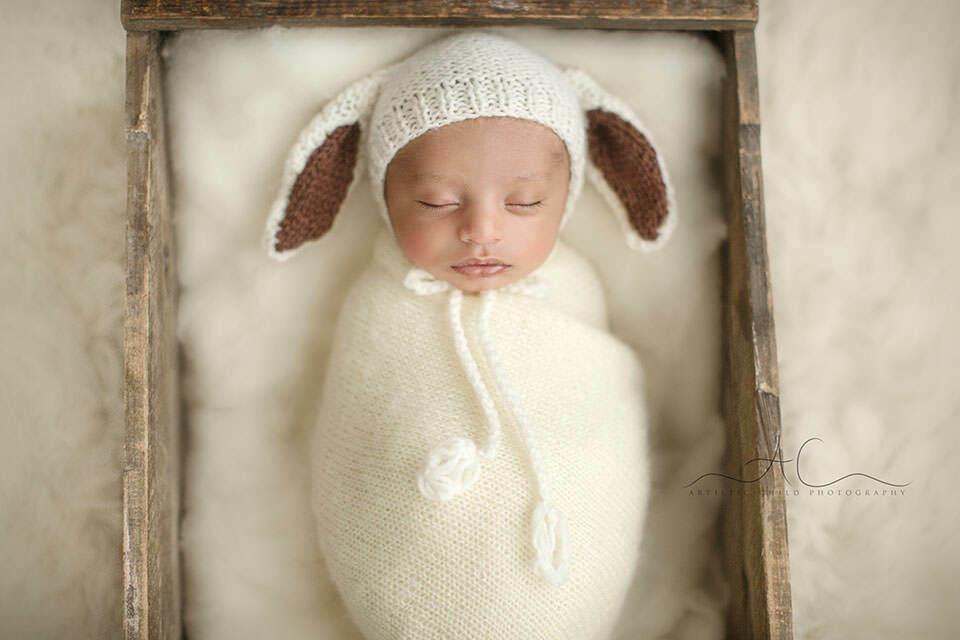 portrait of a newborn baby boy wearing a sheep ear funny hat | London