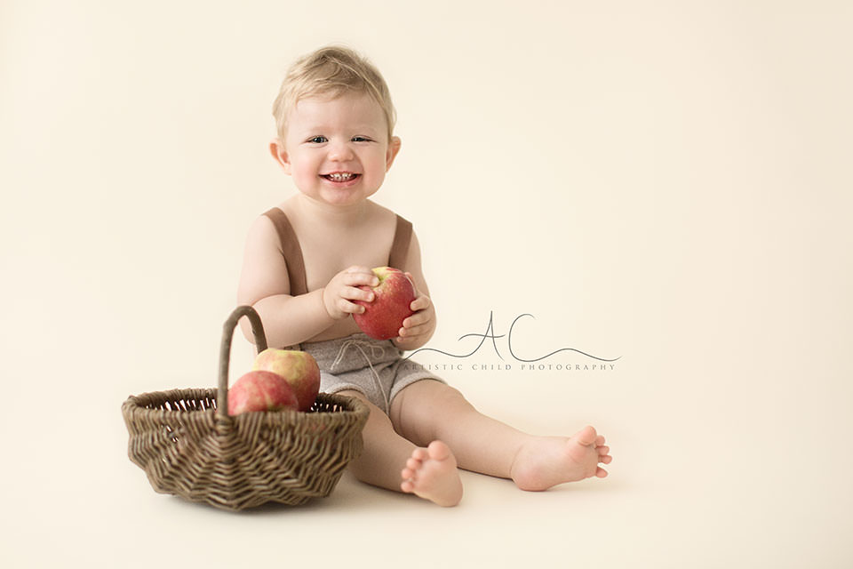 1 year old toddler boy playing with wicker basket full of apples | London