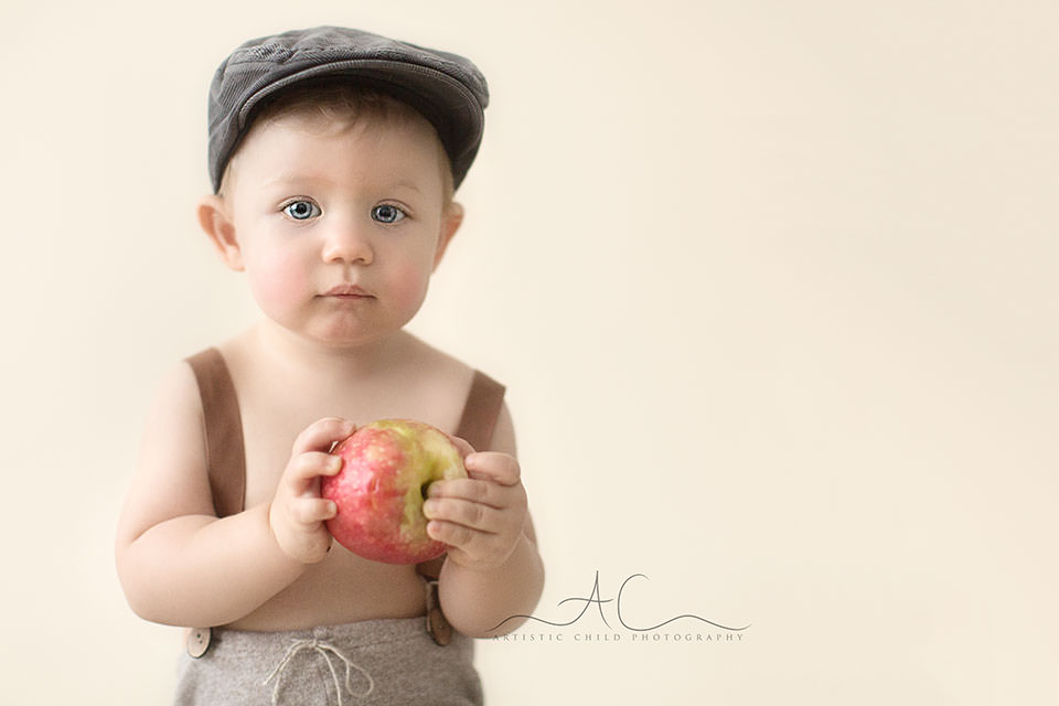 a portrait of a 1 year old toddler boy holding a red apple | London