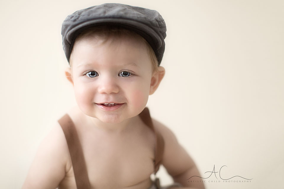 close up portrait of a 1 year old toddler boy wearing a flat cap | London