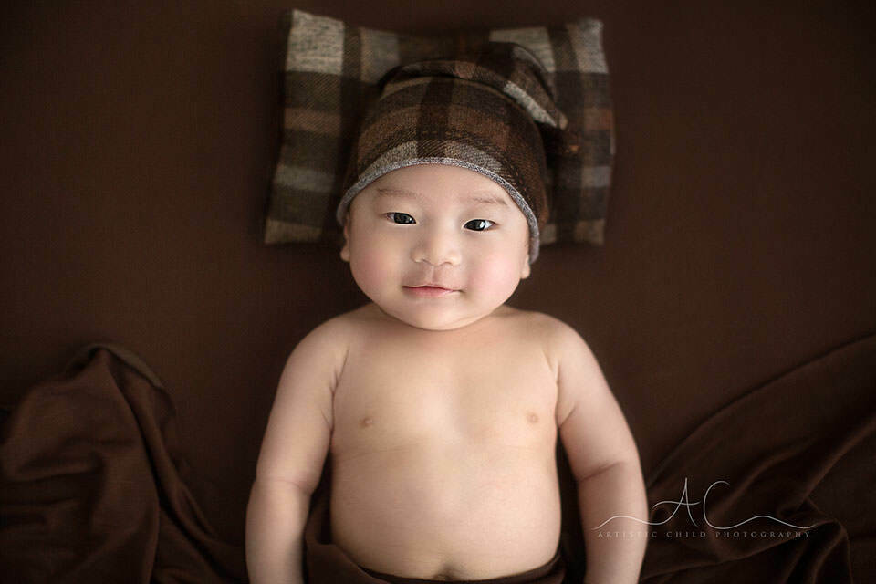 London Baby Boy Photography | portrait of a 3 months old baby boy wearing a brown checked sleepy hat