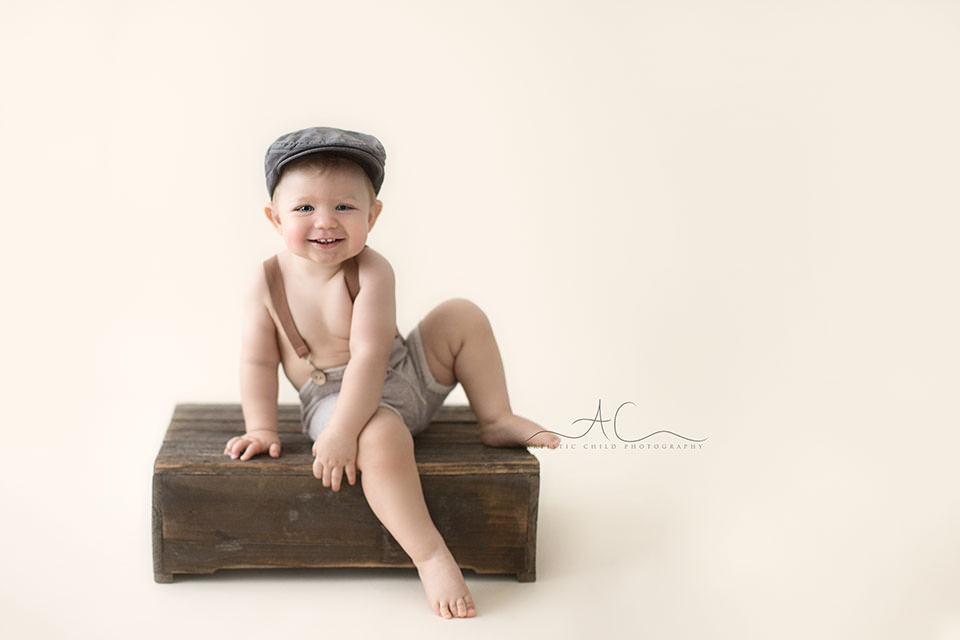 Professional London Toddler Photography Offer | 1 year old toddler boy sitting on top of the wooden crate
