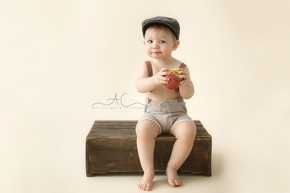 Professional London Toddler Photography Offer | 1 year old toddler boy wearing shorts with braces and a flat cap
