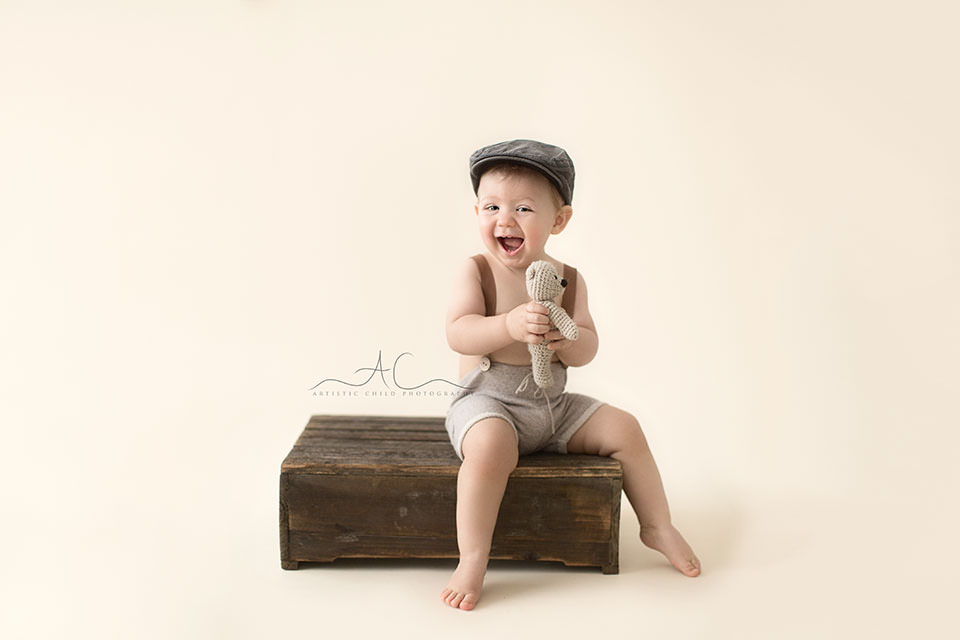 Professional London Toddler Photography Offer | 1 year old toddler boy laughing while holding a small teddy bear