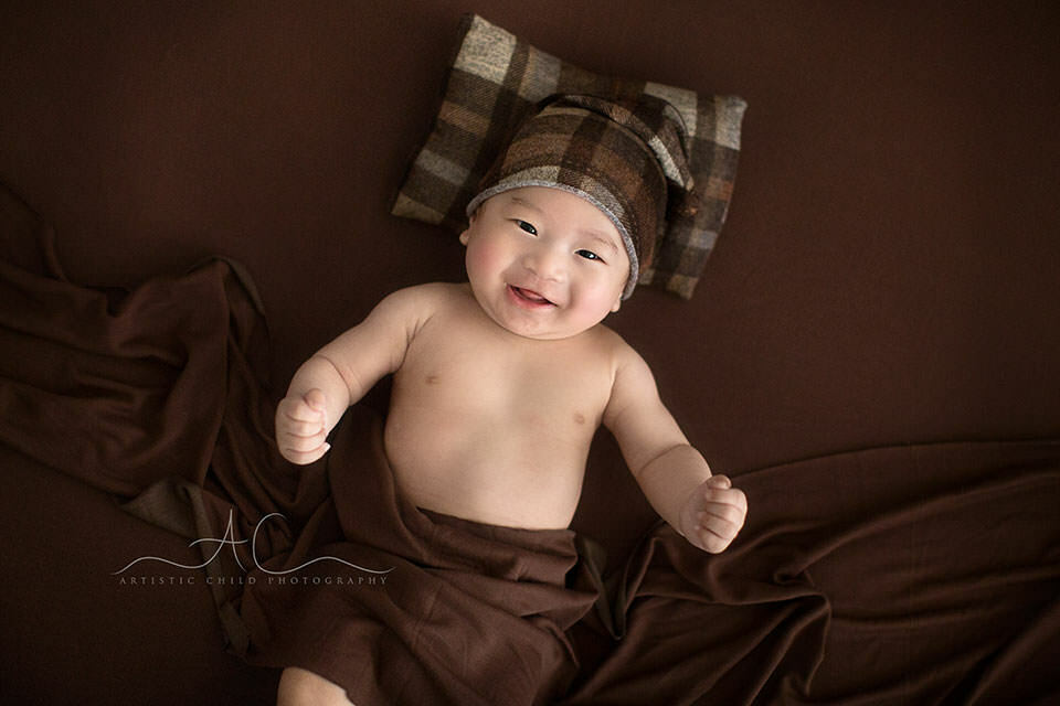 3 months old baby boy smiling while wearing a checked sleepy hat