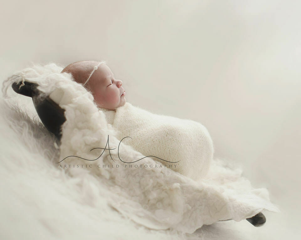 Bromley Newborn Photography Offer   side portrait of a newborn baby girl sleeping in a wooden trench bowl