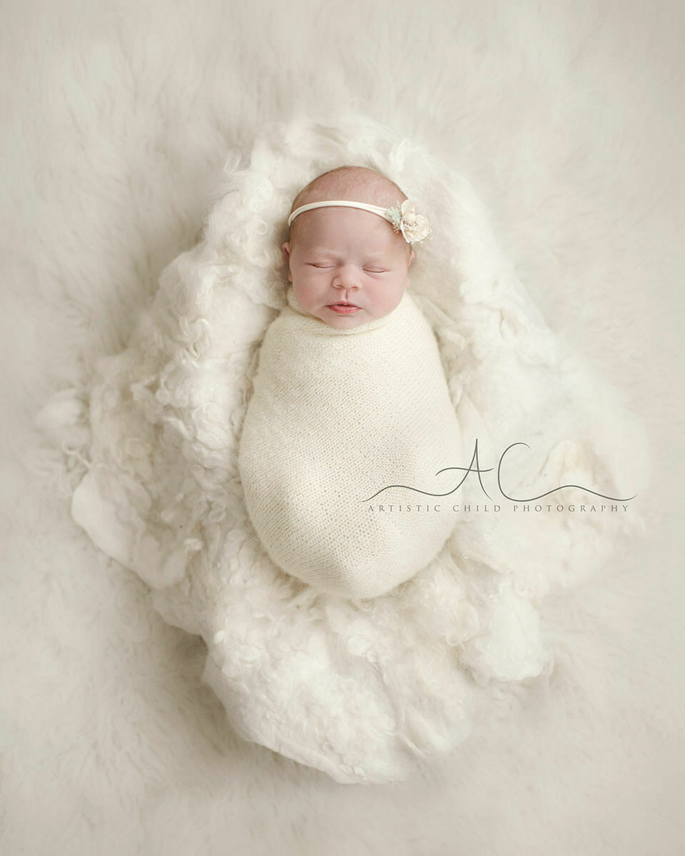 Bromley Newborn Photography Offer | portrait of a newborn baby girl sleeping in a wooden trench bowl on white flokati