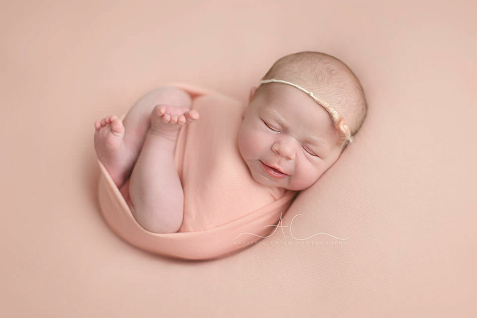 portrait of a newborn baby girl sleeping on a pink backdrop   London