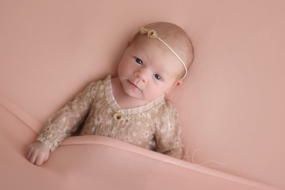 portrait of an awake newbon baby girl photographed on a pink background | London