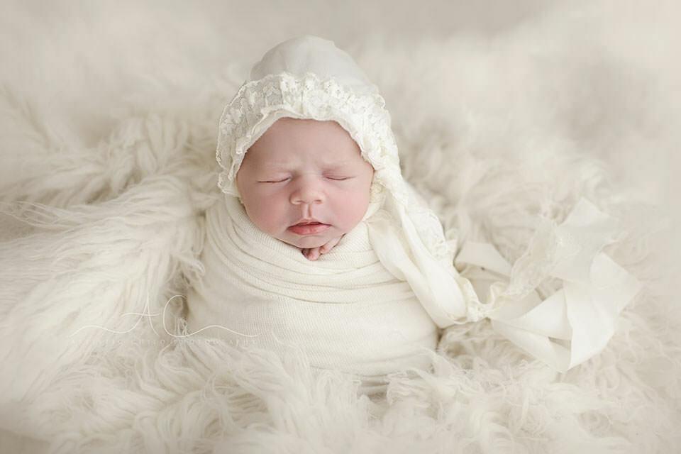 portrait of a newborn baby girl wearing a cute hand made bonnet   London