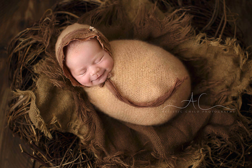 portrait of a newborn baby girl smiling while sleeping in a newborn posing nest | London