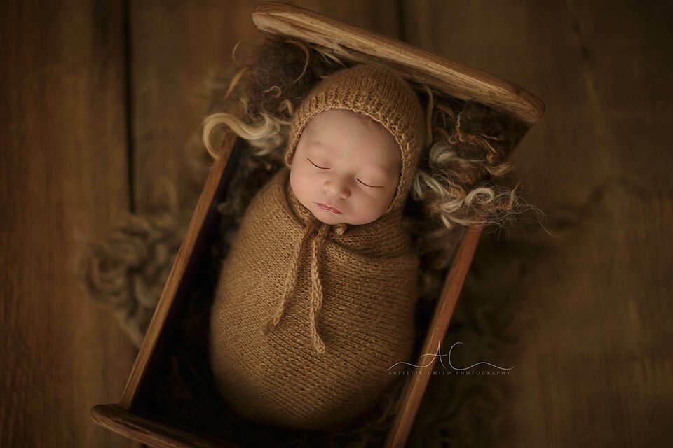 newborn baby boy sleeping in a little wooden bed   London