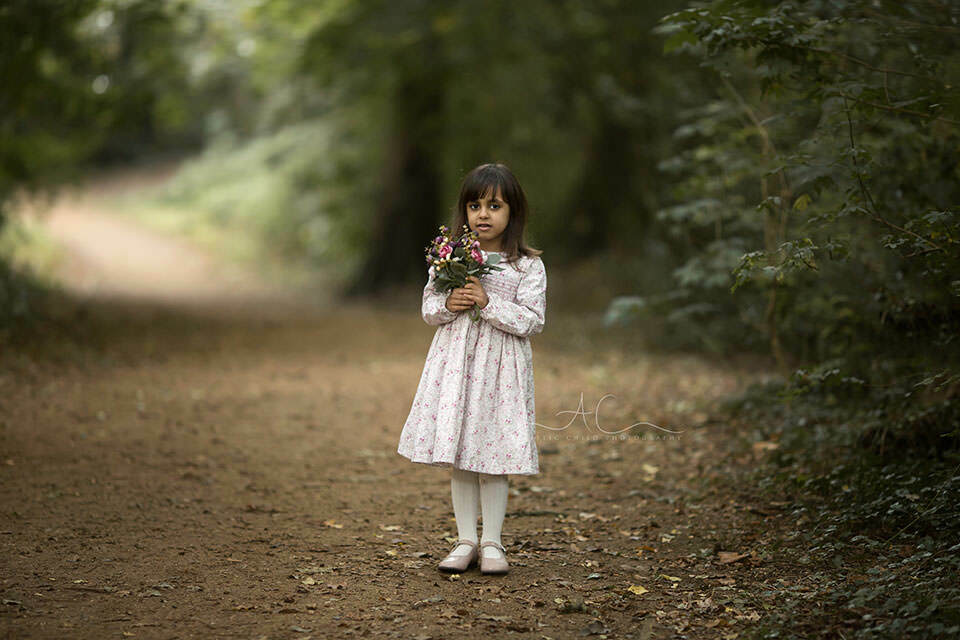 South East London Kids Photography | 5 year old girl holding a bunch of flowers in the woodland looking park