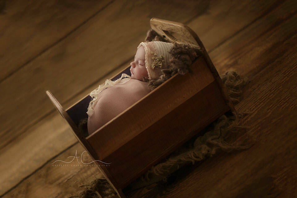 South East London Newborn Baby Girl Photographer | side portrait of a newborn baby girl sleeping peacefully in a tiny wooden bed prop