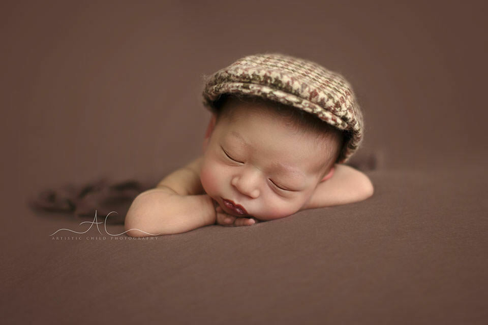 Top London Newborn Images | newborn baby boy wearing a checked flat cap
