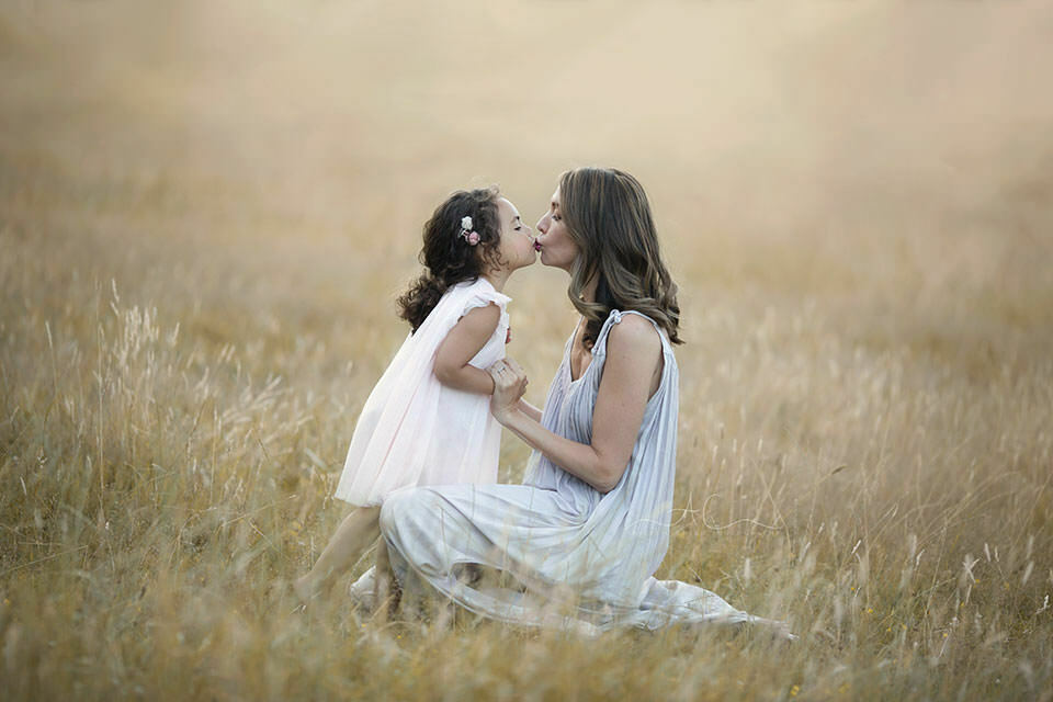 Professional London Family Portraits | mum kissing her 3 year old daughter in grass field