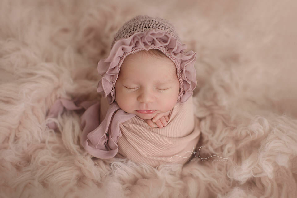 portrait of a newborn baby girl posed in a potato sack pose on the pink flokati during a professional newborn photoshoot in London