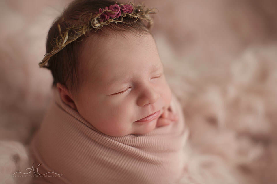 a close up portrait of a newborn baby girl swaddled in pink wrap taken during the newborn photo session in London