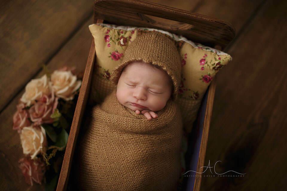 newborn baby girl sleeping swaddled in the tiny wooden bed prop | London
