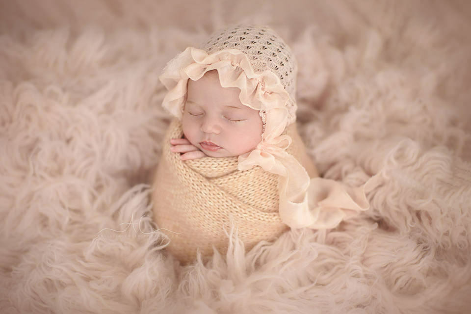 portrait of a 3 weeks old baby girl posed in a potato pose | London