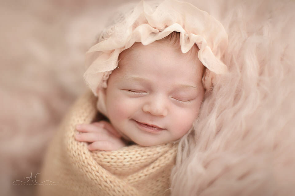 a close up portrait of a 3 weeks old newborn baby girl wearing a cute bonnet | London