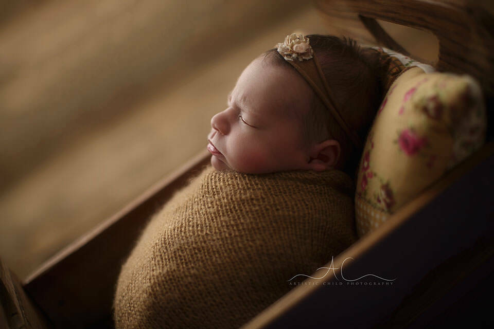 Bromley Newborn Baby Photography Services | a backlit profile portrait of a newborn baby girl sleeping swaddled in the small wooden bed prop