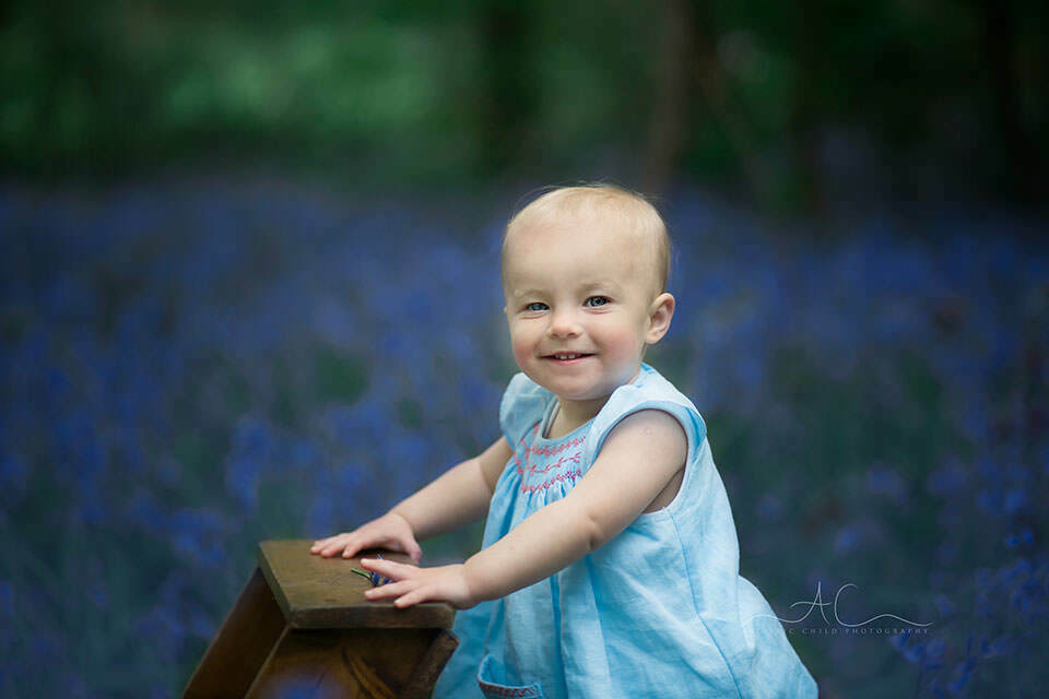 1 year old little toddler girl smiling with bluebells in the background