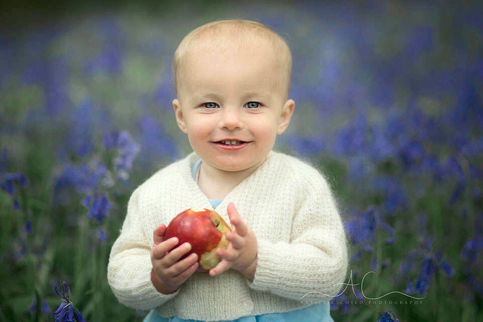 South East London Toddler Photography Services | 1 year old baby girl holding an apple and smiling
