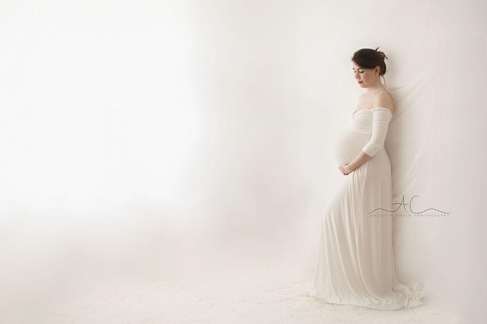 maternity portrait of a pregnant women wearing a long white dress | London