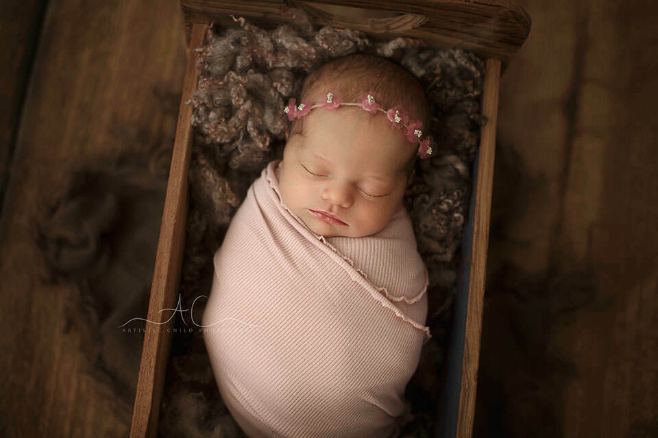 a close up portrait of a newborn baby girl wearing a little flower pink hairband | London