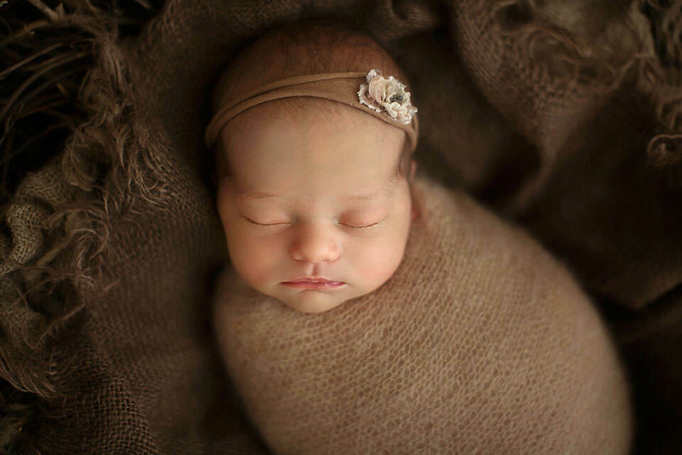 a close up portrait of a newborn baby girl wearing a cute little hairband | London