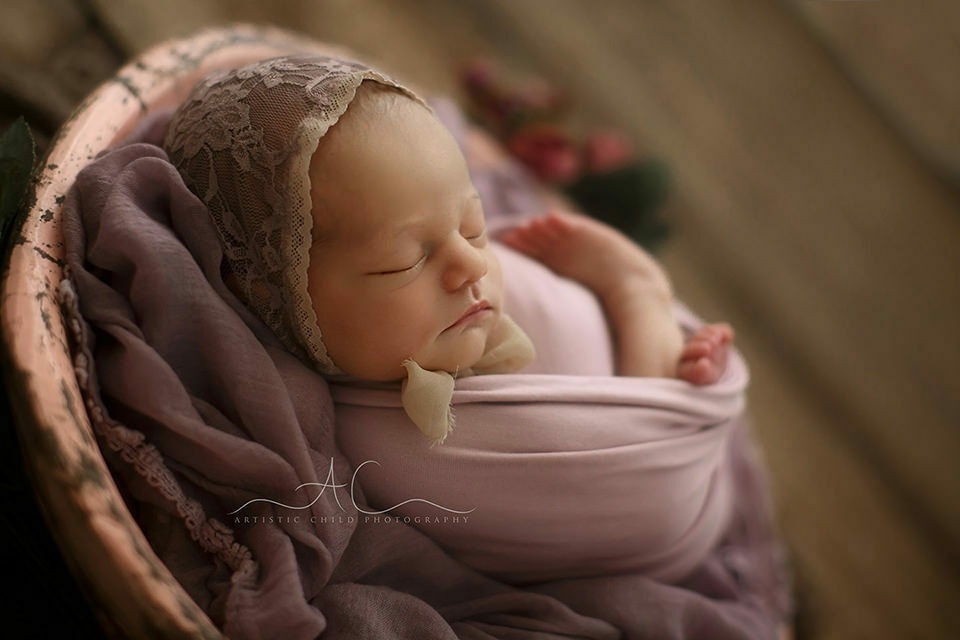 Bromley Newborn Baby Photography Offer | backlit portrait of a newborn baby girl sleeping in a wooden bowl