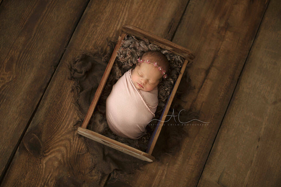 Bromley Newborn Baby Photography Offer | newborn baby girl sleeping in a tiny wooden bed prop