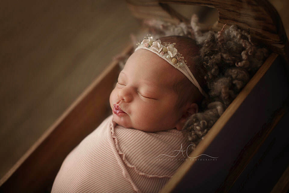 Bromley Newborn Baby Photography Offer | a backlit profile portrait of a newborn baby girl sleeping in a wooden bed prop