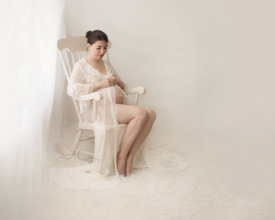 London Maternity Photography Services | portrait of a mum to be looking at her baby while sitting on a rocking chair