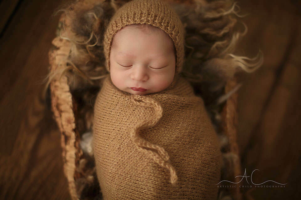 swaddled newborn baby boy photographed in a wooden prop | London