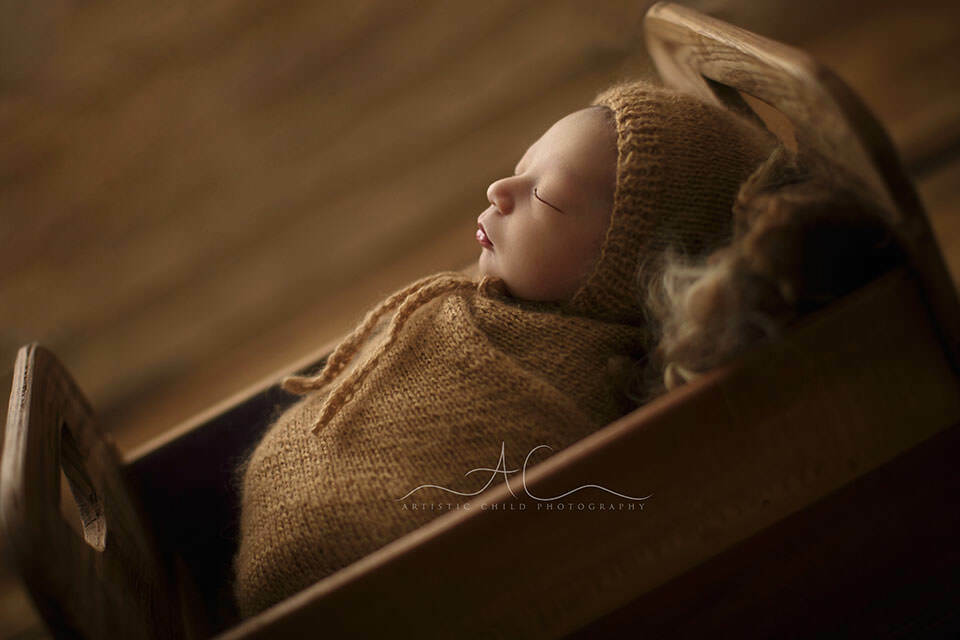 London Newborn Photography Offer | backlit portrait of a newborn baby boy sleeping in a tiny wooden bed prop