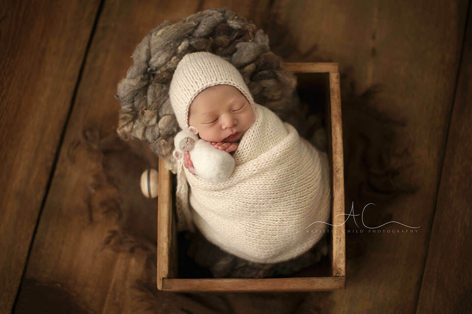 photo of a swaddled newborn baby boy sleeping in an old drower prop | London