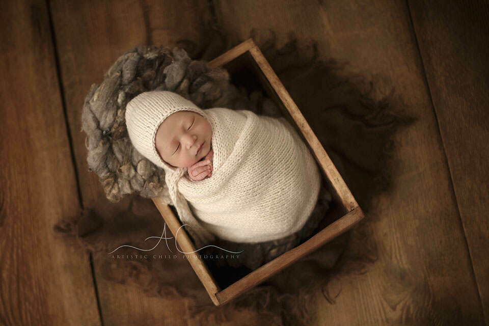 portrait of a swaddled newborn baby boy sleeping in a wooden crate prop | Londony