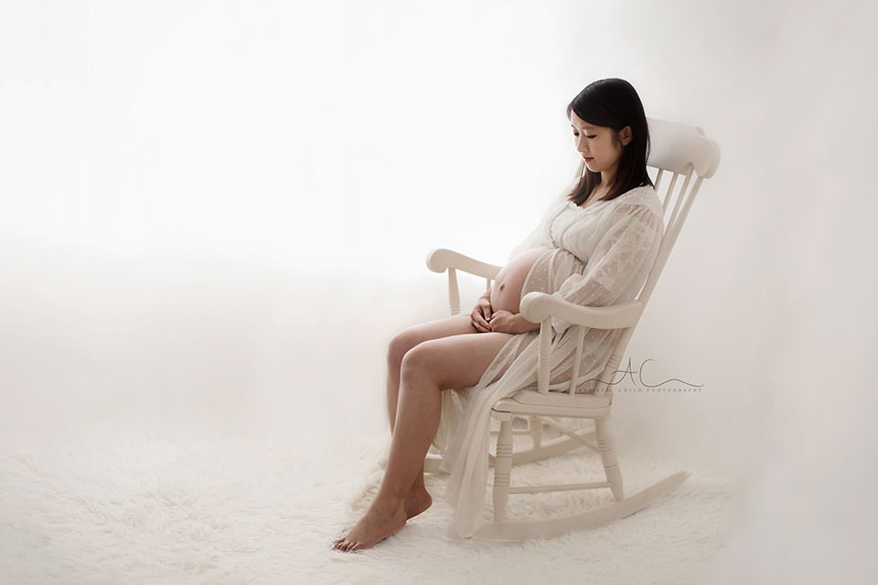 Professional London Maternity Images | pregnant woman sitting on a white wooden rocking chair