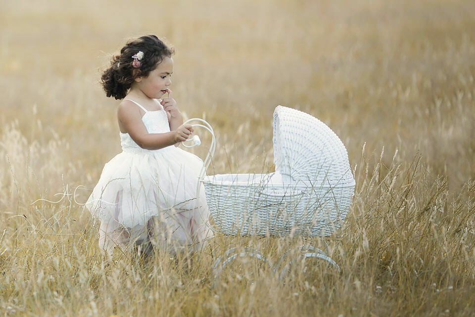 South East London Children Pictures | 3 year old little girl walking with white pram in the grass field