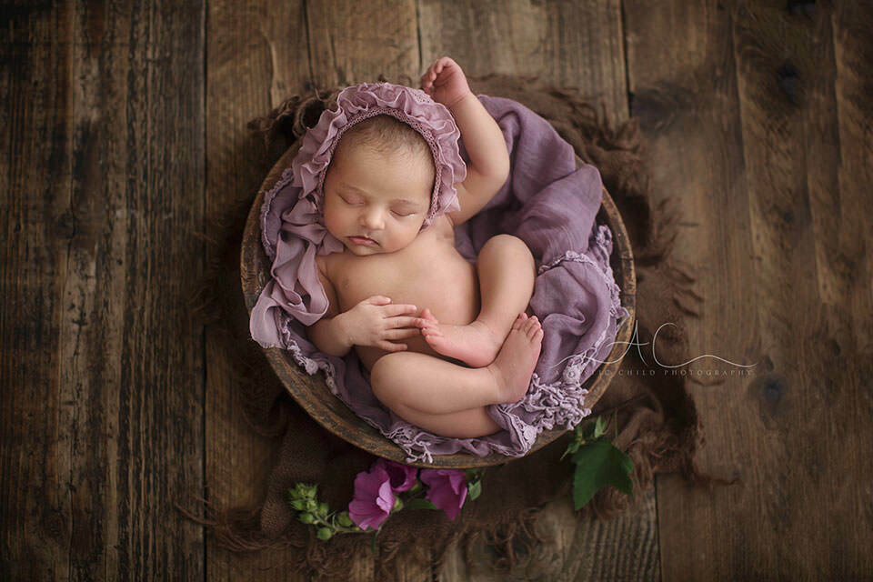 newborn baby girl sleeping in a tiny wooden bowl during her newborn photo session | London