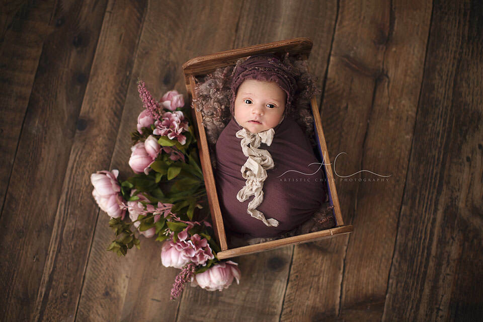 awake newborn baby girl photographed in a tiny wooden bed prop during her newborn photo session | London