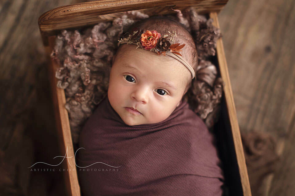 a close up portrait of a newborn baby girl looking strait into camera | London