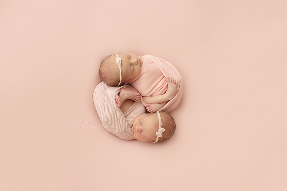 London Newborn Twins Pictures | twin baby girls photographed together on a pink backdrop