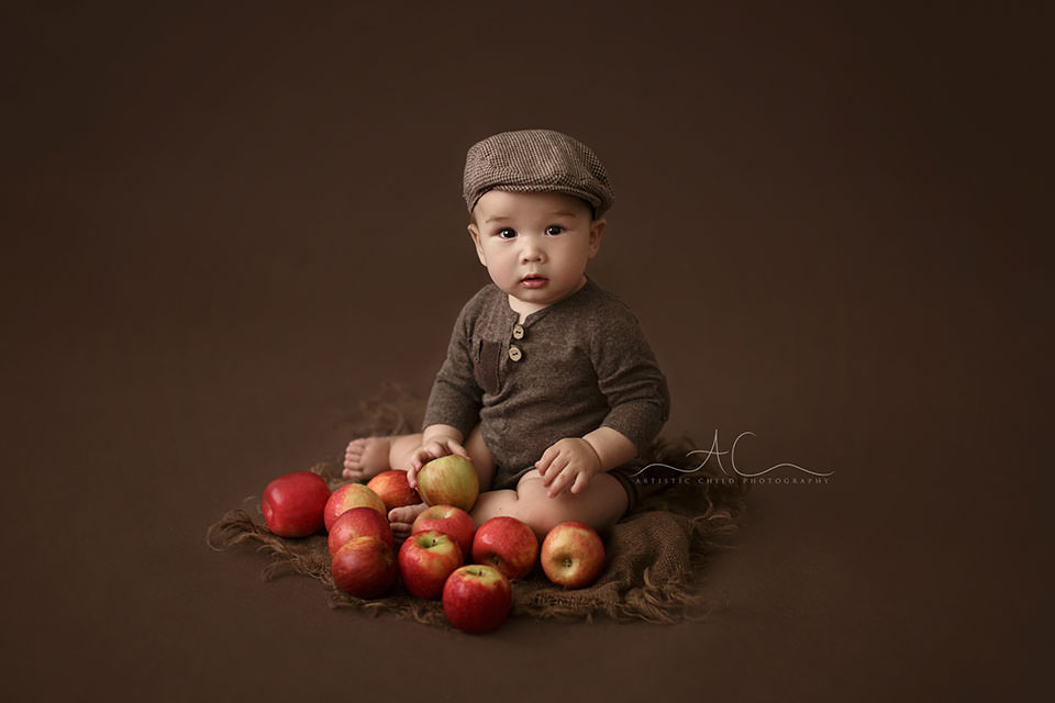 South East London Baby Photography Services | 7 months old baby boy photographed while playing with red apples